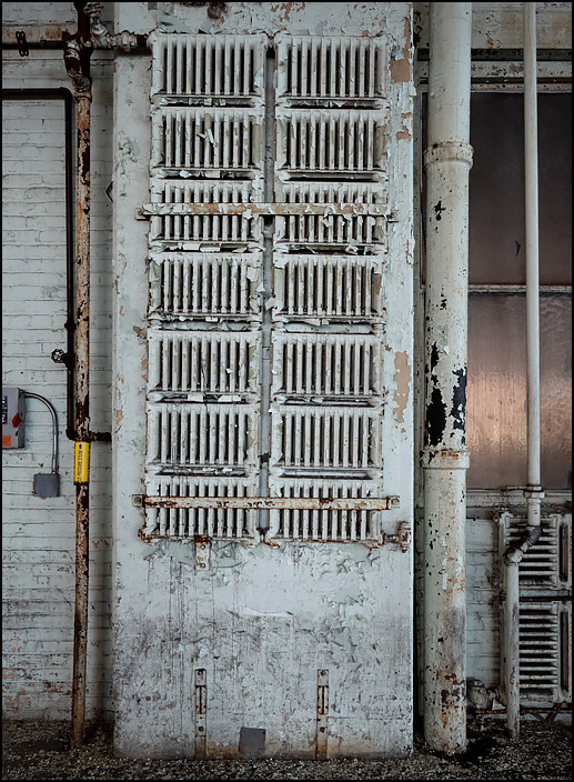Steam heating radiators cover a large part of a the wall in one of the buildings in the abandoned General Electric factory complex on Broadway in Fort Wayne, Indiana.