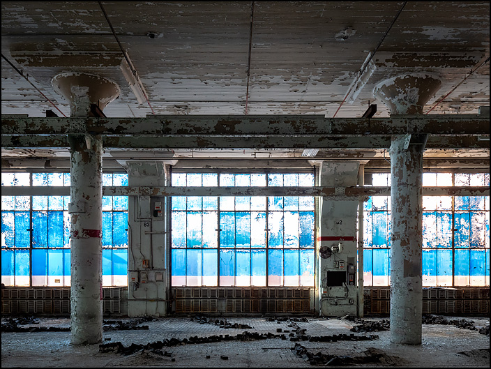 Blue windows and concrete pillars in a large empty space in one of the buildings in the abandoned General Electric factory complex on Broadway in Fort Wayne, Indiana. The wood blocks on the floors were raised up in lines that looked like mole tracks in a yard. The columns hold steel rails that were used to transport machinery.