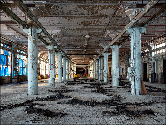 A vast empty hall with rows of concrete columns in one of the buildings in the abandoned General Electric factory complex on Broadway in Fort Wayne, Indiana. The wood blocks on the floors were raised up in lines that looked like mole tracks in a yard.