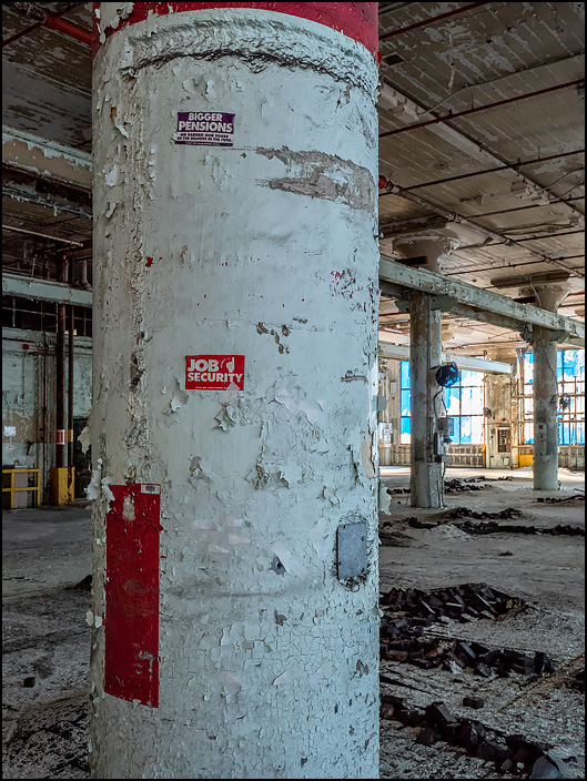 Labor union stickers on a concrete column that is covered in peeling paint in one of the buildings in the abandoned General Electric factory complex on Broadway in Fort Wayne, Indiana. Job Security and Bigger Pensions.
