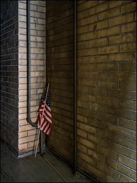 A small American flag leaned against a brick wall in a darkened storage room behind the gymnasium in the GE Club building at the abandoned General Electric factory complex on Broadway in Fort Wayne, Indiana.