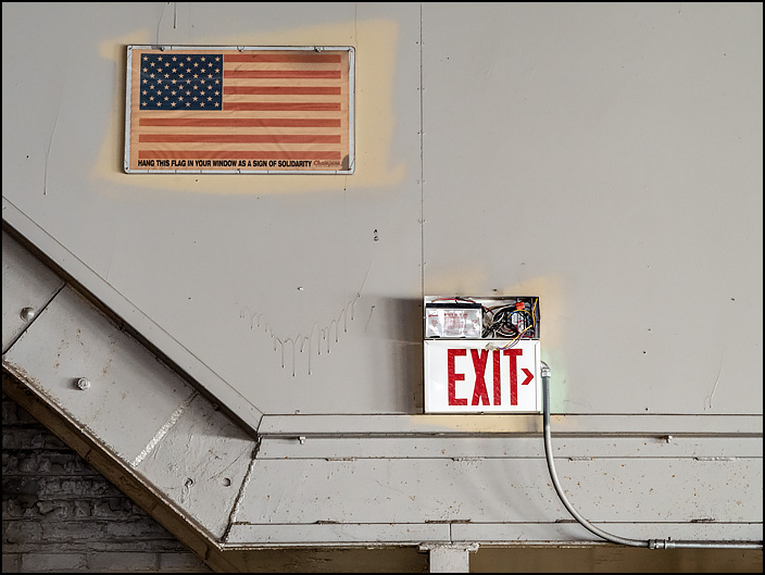 A faded paper American flag on the wall in one of the buildings at the abandoned General Electric factory complex on Broadway in Fort Wayne, Indiana. On the borders of the flag it says, Hang this flag in your window as a sign of solidarity.