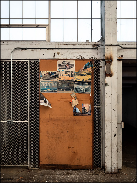 Photos of pickup trucks cut from classic car magazines adorn a door in one of the buildings at the abandoned General Electric factory complex on Broadway in Fort Wayne, Indiana.