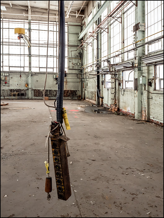 A control box for an overhead crane hangs on a thick cable from the ceiling of one of the buildings at the abandoned General Electric factory complex on Broadway in Fort Wayne, Indiana.