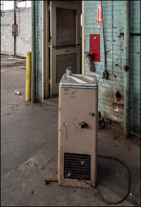 Drinking fountain in front of the mens restroom in Building 22 at the abandoned General Electric factory complex on Broadway in Fort Wayne, Indiana.