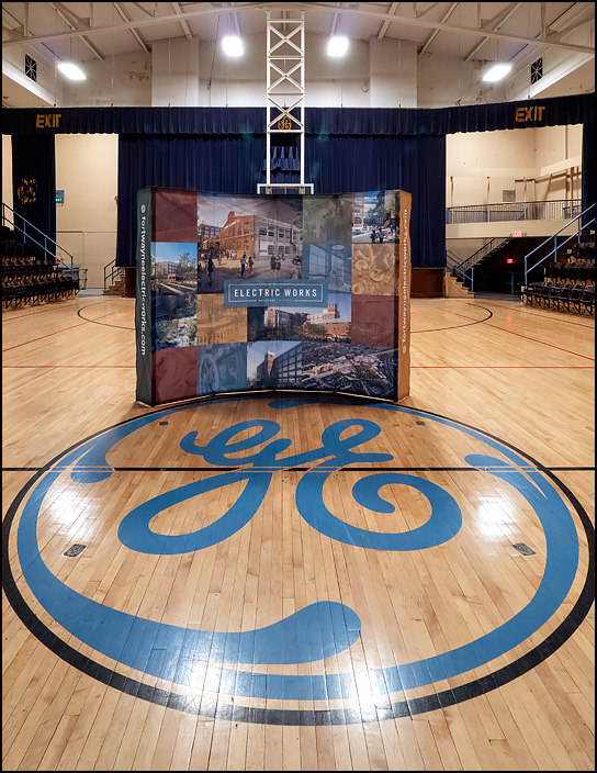 A large sign advertising the Electric Works project stands in the middle of the gym, behind the GE logo on the floor, in the GE Club building at the former General Electric factory complex in Fort Wayne, Indiana.