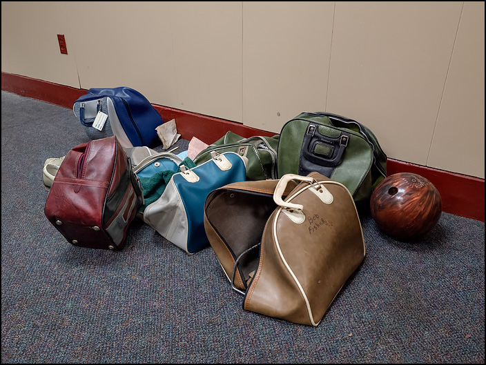 Bowling bags and bowling balls that had been left behind in the GE Club bowling alley on Swinney Avenue in Fort Wayne, Indiana. One of the bags has the name of a former General Electric worker, Bob Fisher, written on it in black marker.