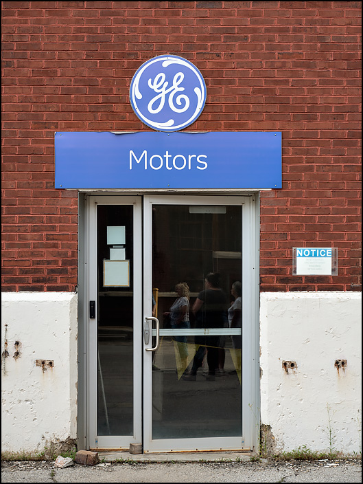 The entrance to Building 26 at the former General Electric factory complex on Broadway in Fort Wayne, Indiana. A GE Motors sign above the door to the brick building has the GE logo.