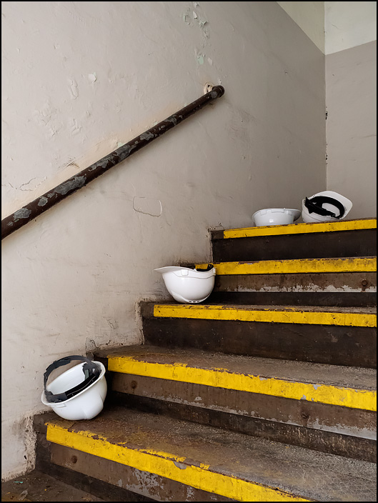 Several white hardhats lay on the stairs just inside the entrance to Building 26 at the former General Electric factory complex on Broadway in Fort Wayne, Indiana.