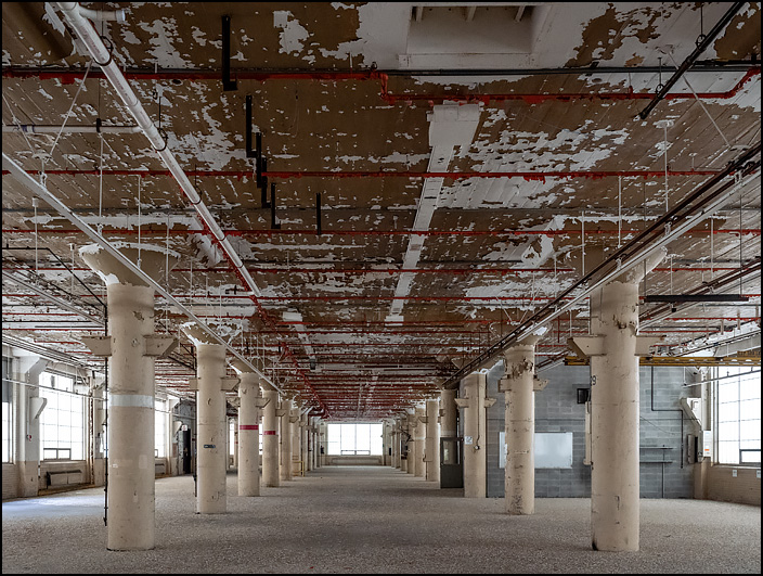 An empty factory floor in Building 26 at the former General Electric factory complex on Broadway in Fort Wayne, Indiana. Paint peels from the ceiling and concrete columns in the huge space, and a thick layer of dust covers the floor.