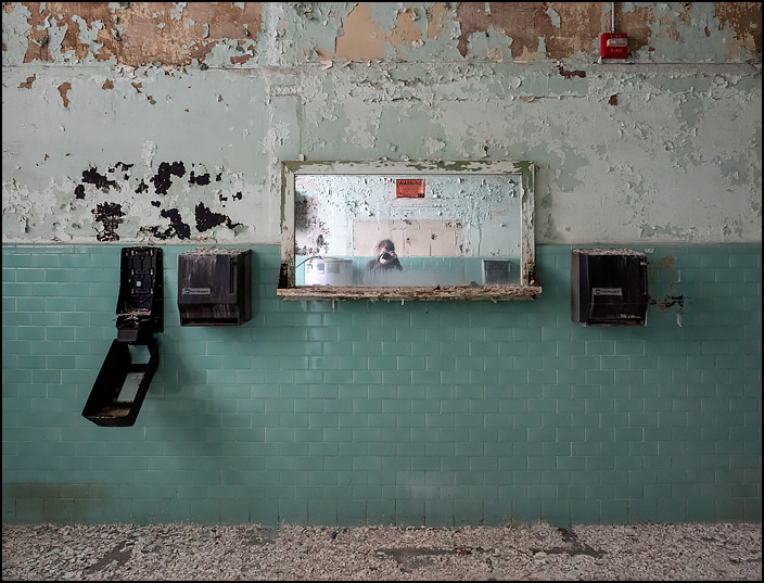 A self portrait of Christopher Crawford in the mirror of a mens restroom in Building 19 at the former General Electric factory complex on Broadway in Fort Wayne, Indiana. The walls are covered in peeling paint and green ceramic tiles. The mirror is flanked by soap and paper towel dispensers.