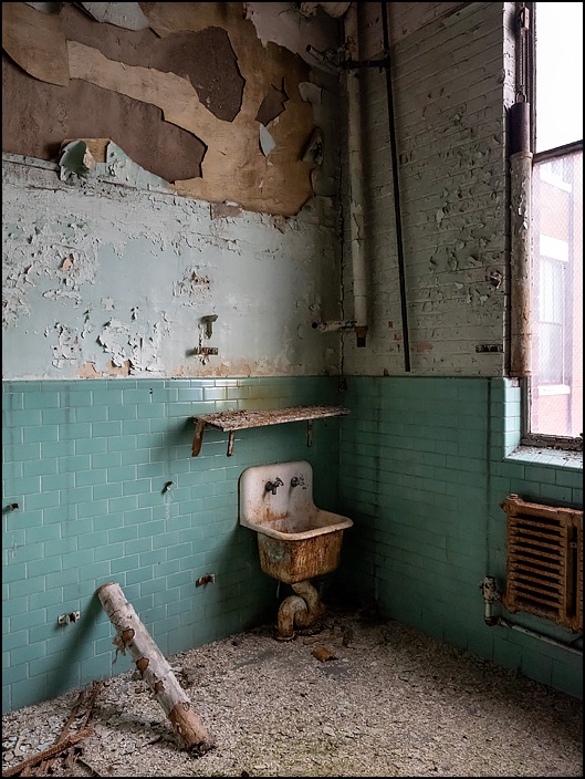 An old cast iron sink with two small faucets in a mens restroom in Building 19 at the former General Electric factory complex on Broadway in Fort Wayne, Indiana. The walls are covered in peeling paint and green ceramic tiles, and a broken pipe is leaned against a wall next to the sink.