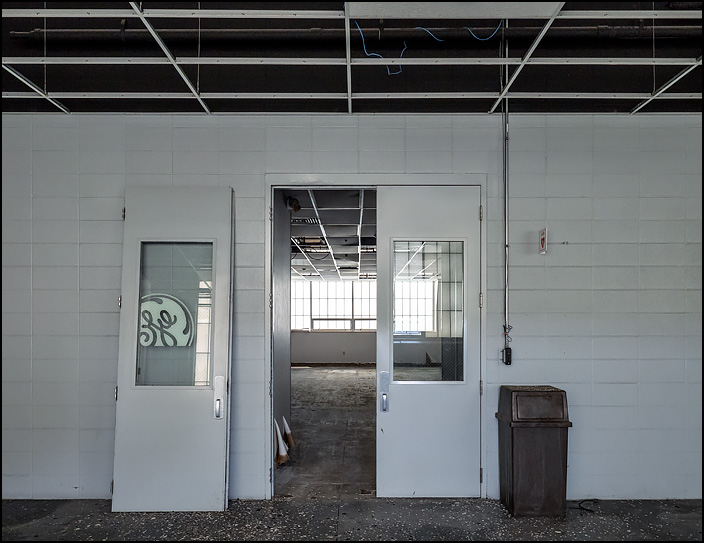 Doors to an office space in building 26 at the former General Electric factory complex in Fort Wayne, Indiana. Most of the drop ceiling tiles in the corridor have been removed and a piece of window glass with the GE logo leans against the wall.