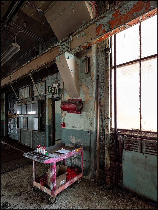 A maintenance cart with several cans of spray paint sits by the windows in one of the buildings in the abandoned General Electric factory complex on Broadway in Fort Wayne, Indiana.