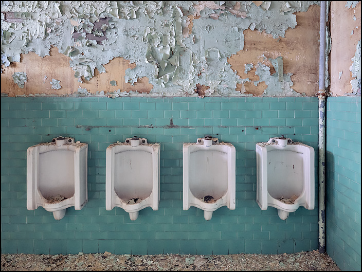 Four urinals on the turquoise tile wall in a mens restroom in building 19 at the former General Electric factory complex in Fort Wayne, Indiana. Paint is peeling from the walls above the urinals, and the floor is covered in broken paint chips.