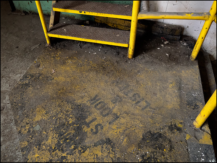 A workplace safety message stenciled on the floor next to some steps on the first floor of building 19 at the former General Electric factory complex in Fort Wayne, Indiana. It says Stop Look and Listen.