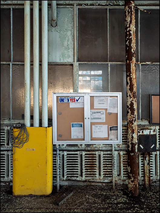 A display case with workplace safety signs and union information hangs on the wall above the heating radiators in one of the buildings in the abandoned General Electric factory complex on Broadway in Fort Wayne, Indiana.