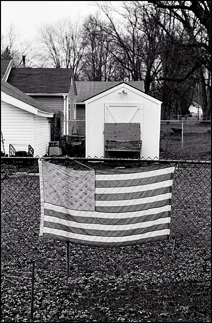 A faded old American Flag hanging on a chain-link fence around the back yard of a house on Geneva Street in Fort Wayne, Indiana.