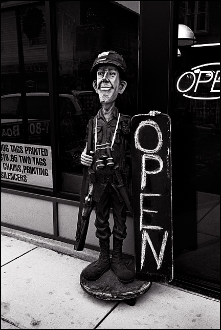 A statue of a soldier in uniform holds the Open sign in front of G I Joe's Army Surplus store on Wells Street in Fort Wayne, Indiana.
