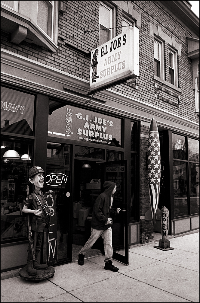 A man in a hoodie walks out the front door of G I Joes Army Surplus store on Wells Street in Fort Wayne, Indiana. A large bomb painted like the American Flag hangs on the old brick storefront and a statue of a soldier holds the Open sign on the sidewalk.