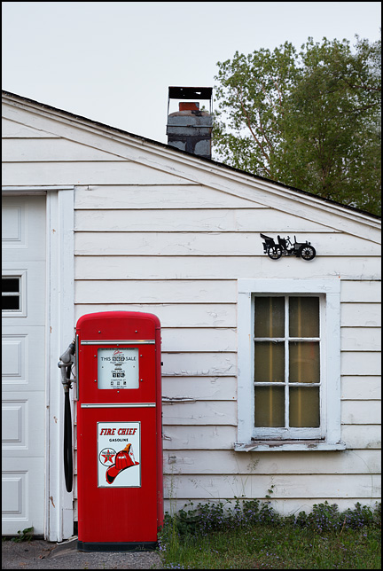 An antique Gilbarco Calco-Meter gas pump with Texaco Fire Chief Gasoline sign in front of a garage at sunset.