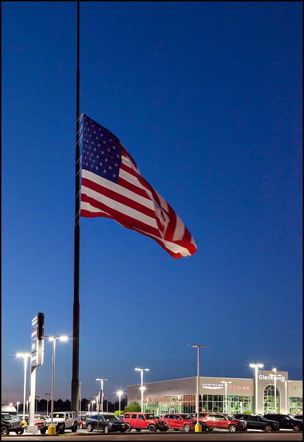 A gigantic American flag flies at half-staff at dusk over Glenbrook Dodge Chrysler Jeep in Fort Wayne, Indiana. The flag was lowered to commemorate the victims of a terrorist attack in France.