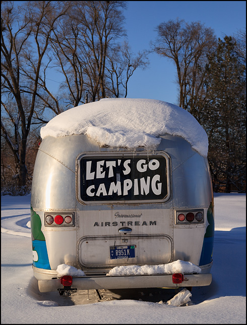 An old Airstream travel trailer with a decal over the rear window that says Lets Go Camping. The camper sits in deep snow during the winter in Indiana.