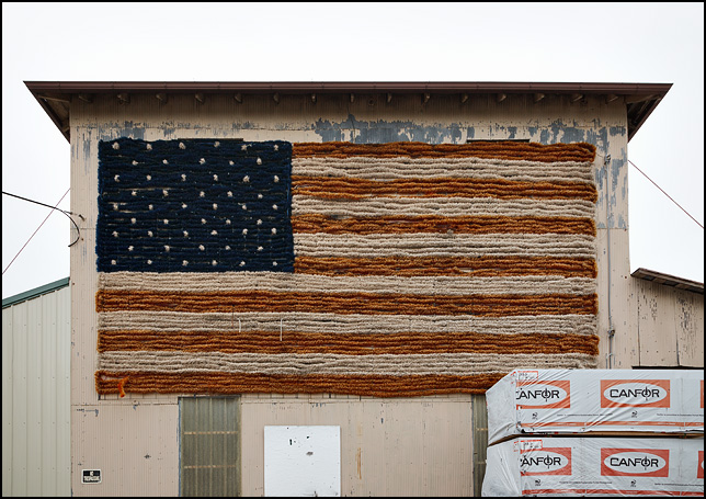 A gigantic American flag made of garland hangs on the front of the Grabill Grain Company in the small town of Grabill, Indiana.