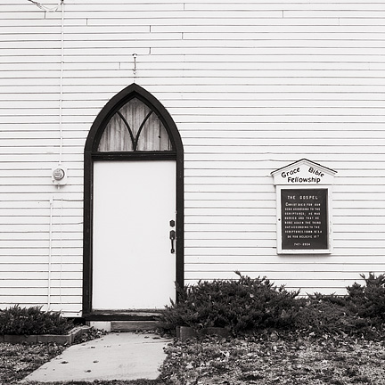 The front door and sign under an arched window on the old white church at the Prairie Grove Cemetery in the Waynedale area of Fort Wayne, Indiana. The sign says Grace Bible Fellowship.