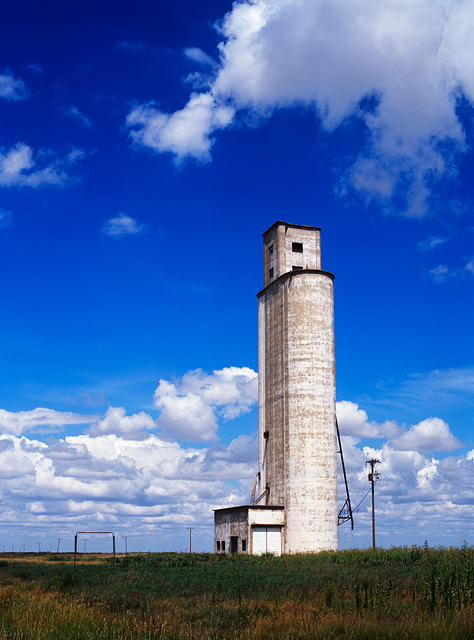 An abandoned grain elevator in the Texas panhandle looks lonely on the flat plains surrounded by tall grass and cornfields under a blue sky full of fluffy white clouds on a sunny day.