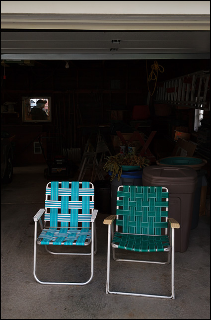 A pair of webbed folding patio chairs sitting side by side in an open garage door.