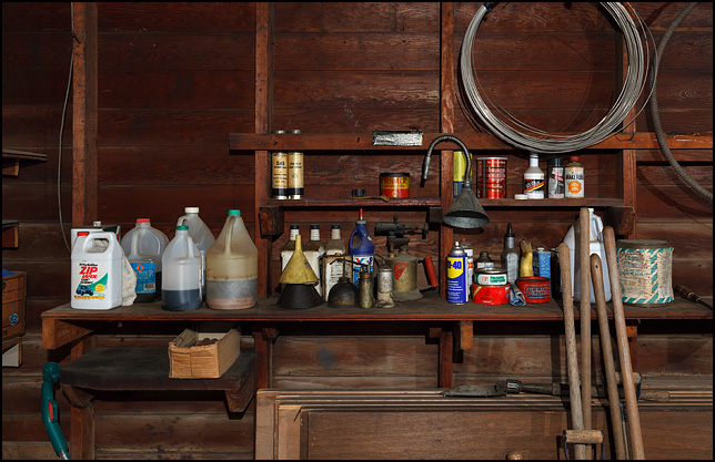 A wooden shelf full of old oil cans, bottles of motor oil, and jugs of automotive fluids in my grandpas old garage.