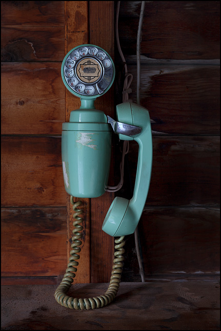 A green Automatic Electric Model 183 Spacemaker rotary telephone hanging on the wall in grandmas old garage.
