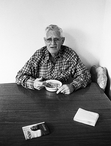 My grandfather, Charles Crawford, eating a bowl of cereal for breakfast at his kitchen table. A prayer book from the Lutheran church sits on the table.