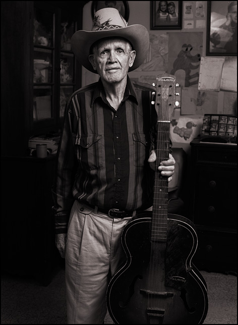 My grandfather Charles Crawford at age 74 wearing a cowboy hat and holding the Harmony guitar that his mother bought him for his 16th birthday.