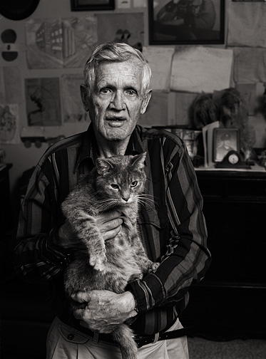 My grandfather Charles Crawford holding his mean old cat. The wall behind him is covered in drawings from his grandchildren.