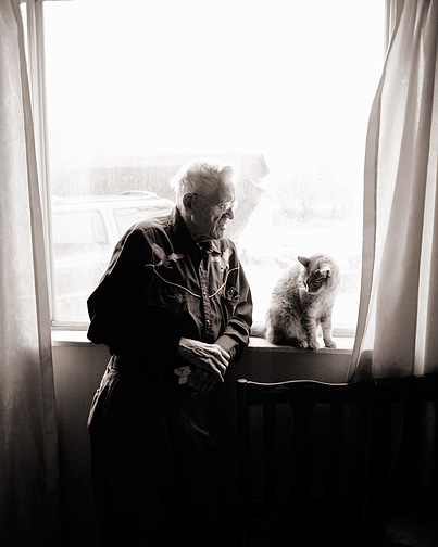 My grandfather, Charles Crawford, talking to his old cat by the window. The cat, Molly, sits on the windowsill looking down at grandpa's hands.
