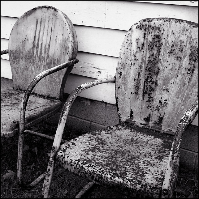 Two old rusty metal motel chairs sit together in the rain next to my grandparents house.