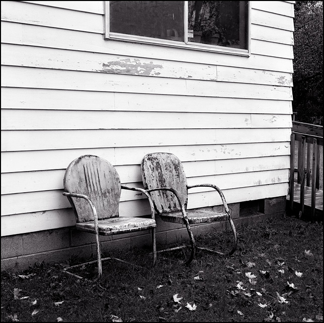 A pair of rusty old metal motel chairs sit in the rain next to my grandparents house.