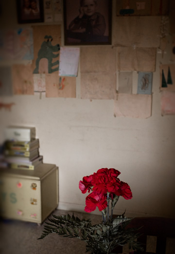 A vase of red roses stands on the dining room table at my grandfather's house. The wall behind them is covered in childrens art.