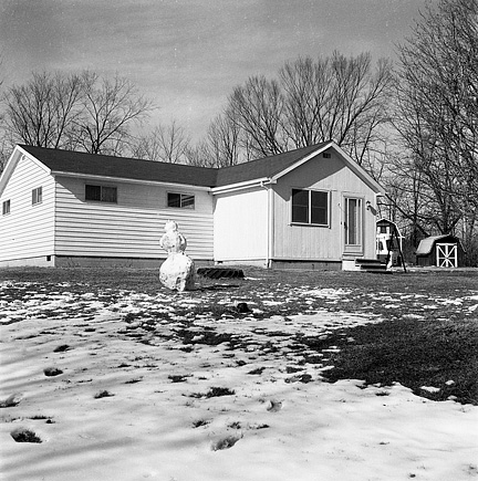 My grandfather's house in winter with a partly melted snowman in the front yard.