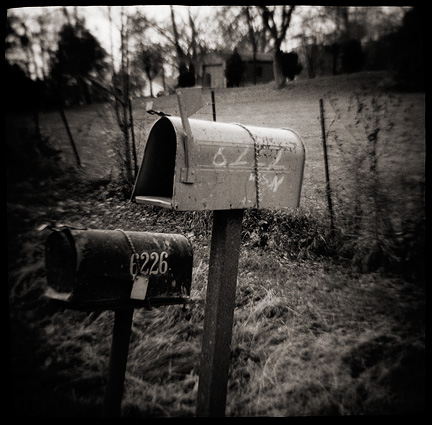 Toy camera photograph of two old mailboxes smashed by baseball bats and held to posts with bungee cords.