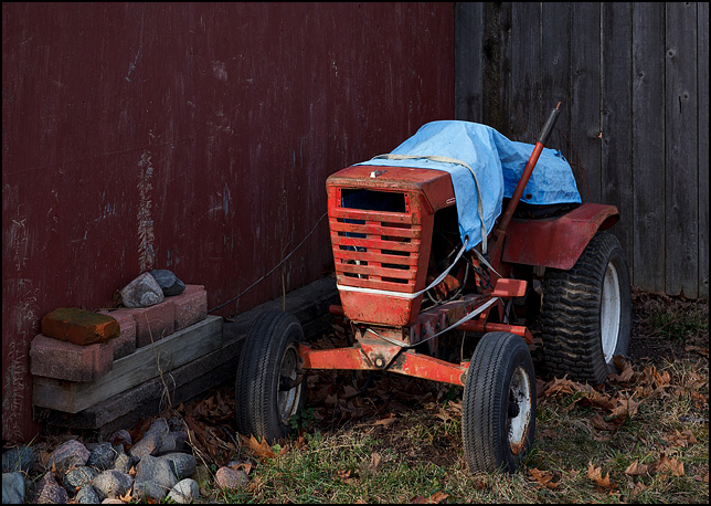 An old Wheel Horse garden tractor sitting next to a red barn.