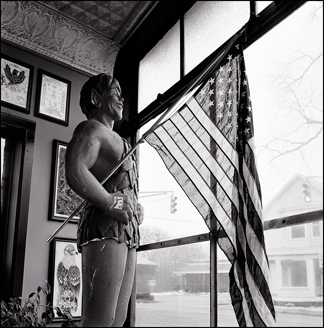 A life-size Styrofoam statue of the Jolly Green Giant stands in the front window of a tattoo shop holding a big American flag.