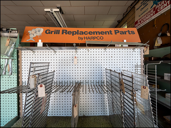 An old display of gas barbecue grill replacement parts at Waynedale Plumbing Supply. The racks are bare, with only a few parts left in stock. A faded sign says, Grill Replacement Parts By HARPCO.