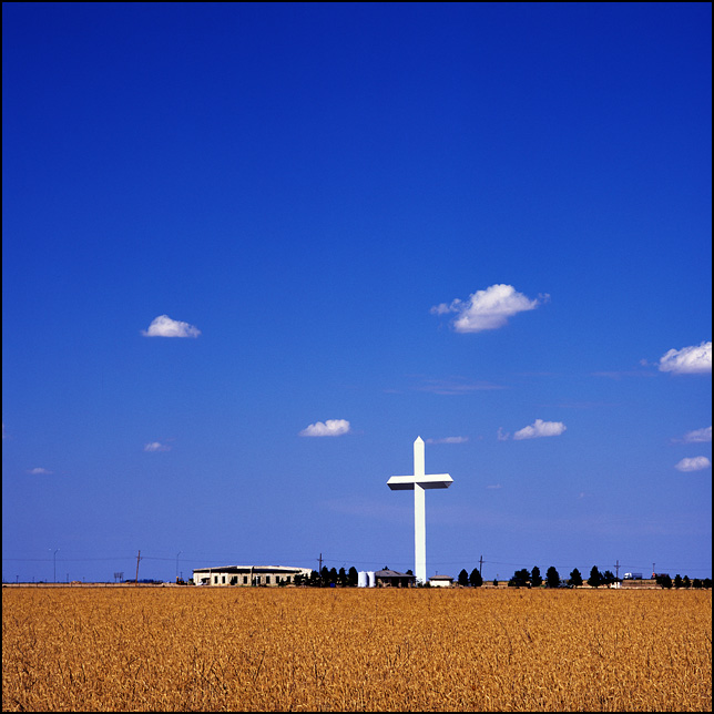 The giant cross along Interstate 40 in Groom, Texas under a deep blue sky over a golden wheat field.