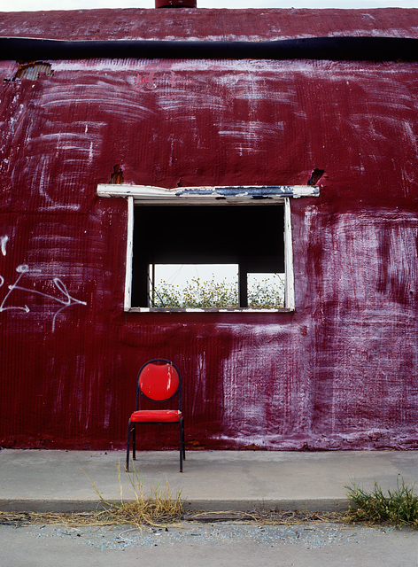 An old red chair sits outside a big red abandoned quonset hut that once housed a gas station and cafe restaurant along Interstate 40 and old Route 66 outside the panhandle town of Groom, Texas. The quonset hut is covered in spray painted graffiti.