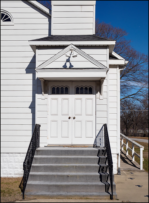 The main entrance to Grovertown United Methodist Church in the small town of Grovertown, Indiana. The church is a small white woodframe building with stairs leading up to the doors.