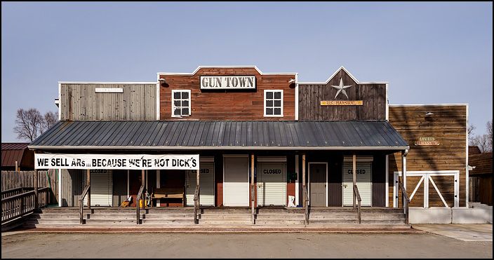 The gun town is a firearms store on US-30 in rural Starke County, Indiana. The building looks like a set of storefronts from an old west cowboy town. The banner says We sell ARs because we're not Dicks.