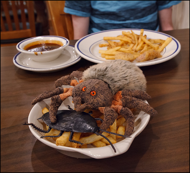 Hairy The Spider, a Ty Beanie Baby, eating a gigantic cockroach on a plate of french fries.